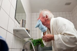 Old Man Cleaning His Face with Towel